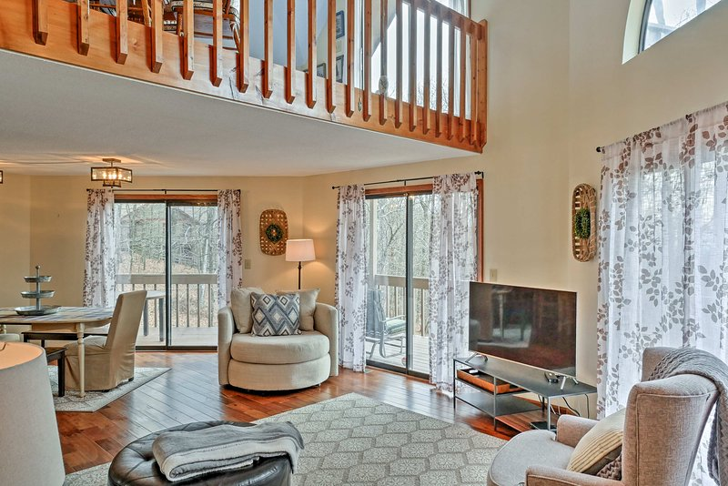 The living room features a flat-screen TV and gas fireplace.