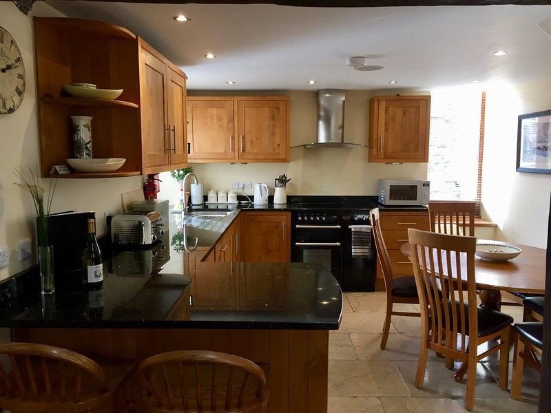 Oak & granite kitchen diner. Range cooker, Portmeirion crockery, flagged floor