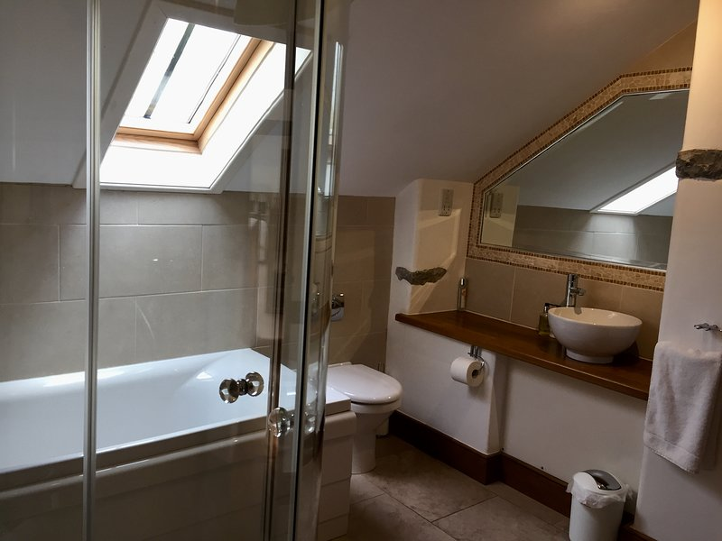 En suite bathroom to first floor bedroom with large bath, separate shower enclosure. Heated floor!