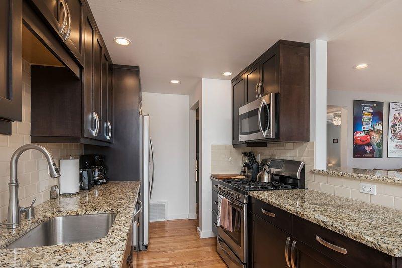 La cocina renovada cuenta con una estufa de gas y electrodomésticos nuevos de acero inoxidable