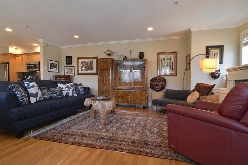 De warme woonkamer beschikt over een groot tv-scherm en veel comfortabele plekken om op te krullen met een goed boek of om te genieten van de kunst