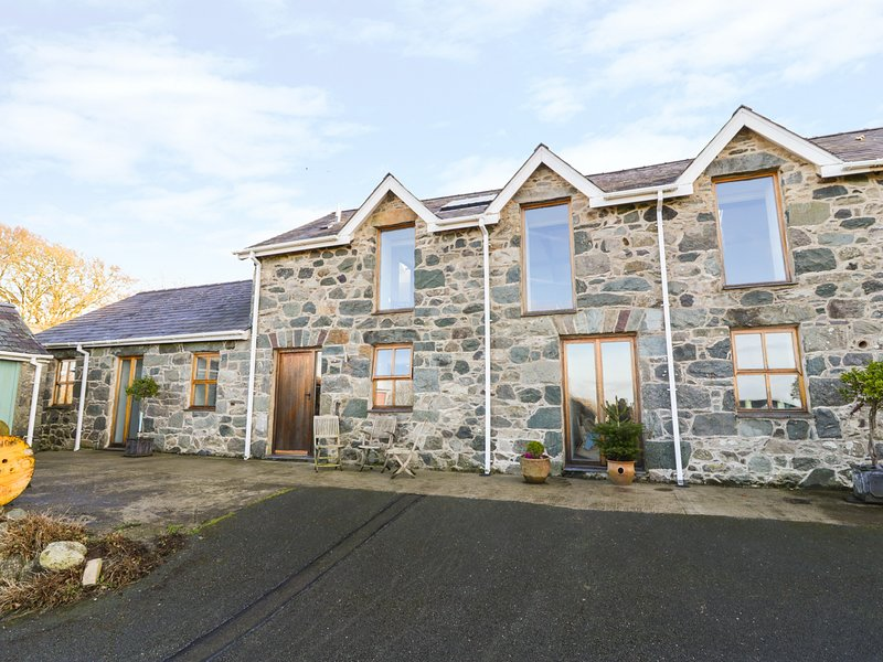 WERN OLAU COTTAGE, exposed beams and stonework, Smart TV, decking with hot tub, vacation rental in Groeslon