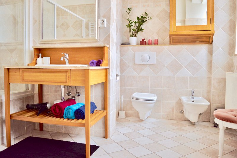 Salle de bains familiale avec baignoire et douche, toilette, bidet et machine à laver.