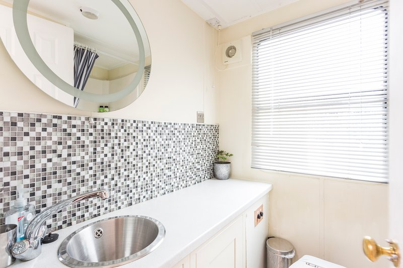 Bathroom with toilet and full size shower plus basin providing hot