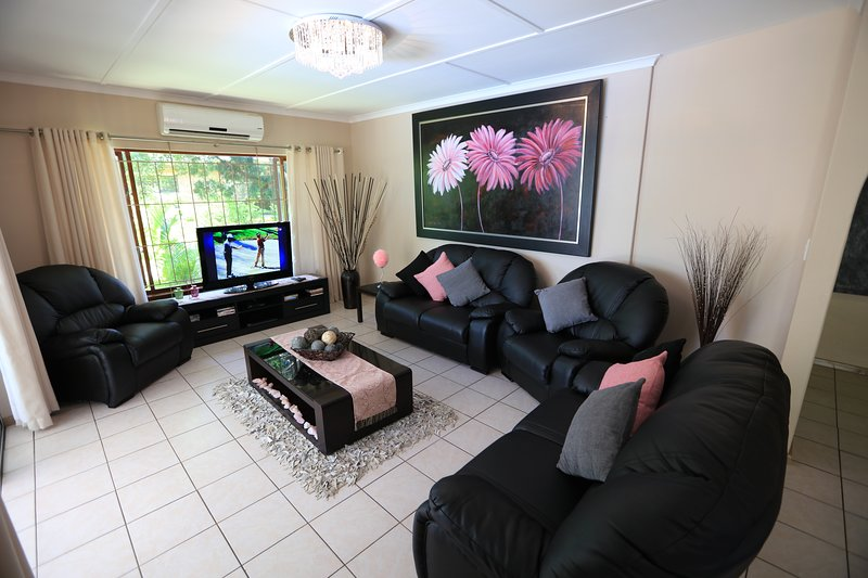 Living room with DSTV, Aircon and sliding doors leading out onto the patio / pool entertainment area