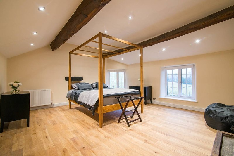 Main bedroom - large, bright, airey space with 4-poster kingsize bed with large flat screen tv