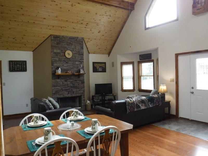 sala de estar con chimenea muebles de cuero y TV de pantalla grande