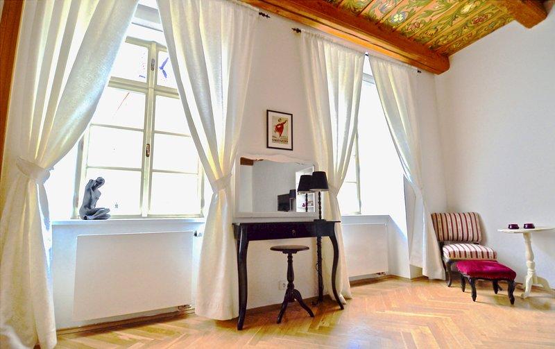 Grandes duas janelas na sala de estar com vista para o Castelo de Praga - elegantes compõem mesa.