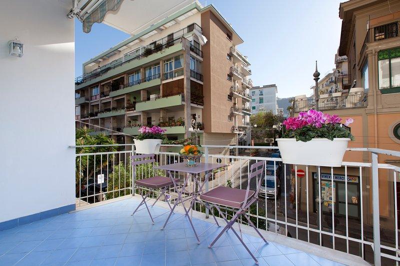 Terrasse avec vue Corso Italia, mobilier d'extérieur et coin repas.