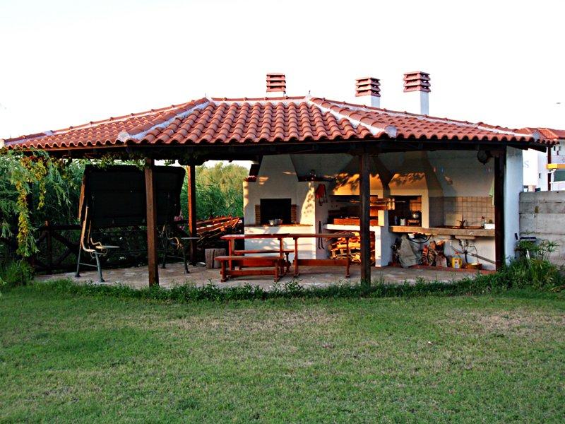 área de churrasco com espaço de jantar no jardim