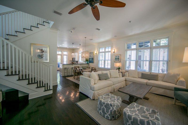 Geräumiges, komfortables Wohnzimmer mit vielen Sitzgelegenheiten, einem Kamin und französischen Türen, die auf die schattige Veranda führen.