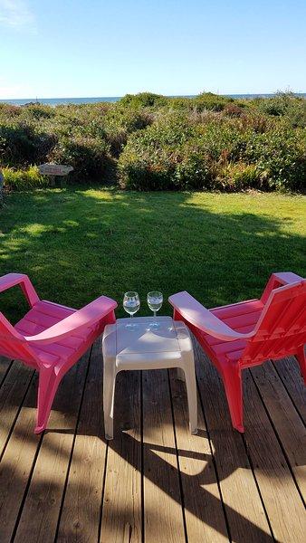 cadeiras no convés, de frente para o mar, quintal gramado com caminho privado à praia