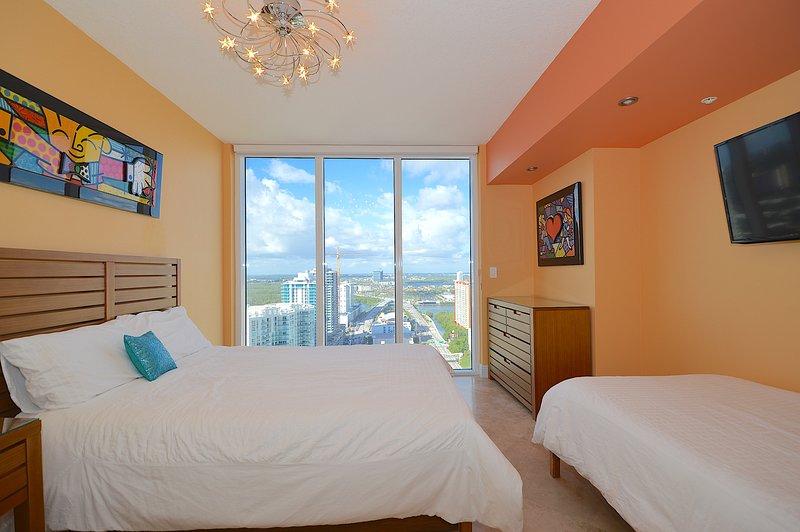 Tweede slaapkamer - uitzicht over de stad en het water, queen bed, en twee aparte bedden.