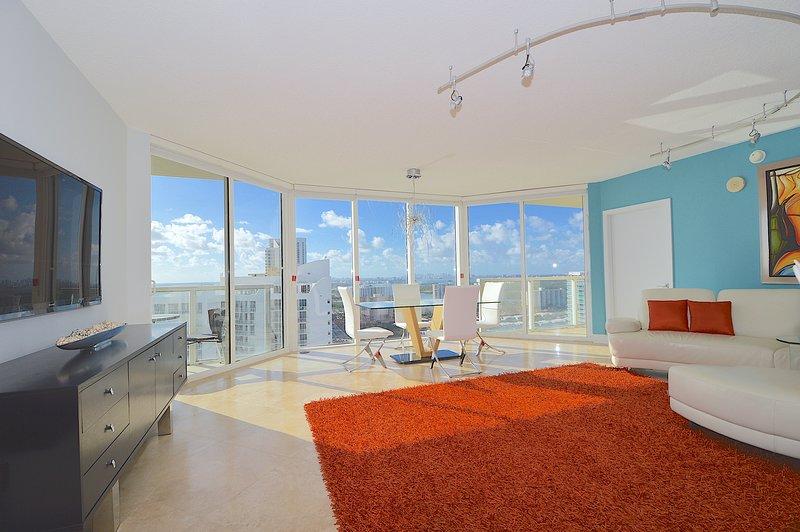 Grote woonkamer met vloer tot het plafond ramen die ton van het zonlicht en een prachtig uitzicht bieden.