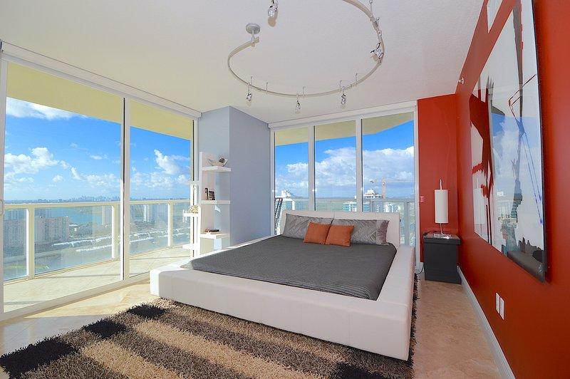 Grote slaapkamer met uitzicht op de oceaan, een kingsize bed, modern decor, toegang tot balkon.