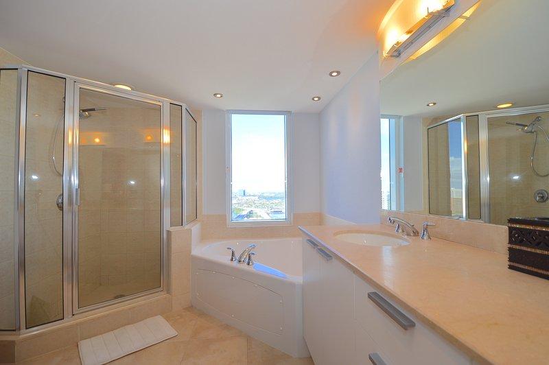 Master badkamer - dubbele wastafel, groot bad, en inloopdouche.