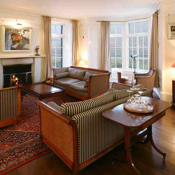 The drawing room with an open fire and stylish comfortable seating