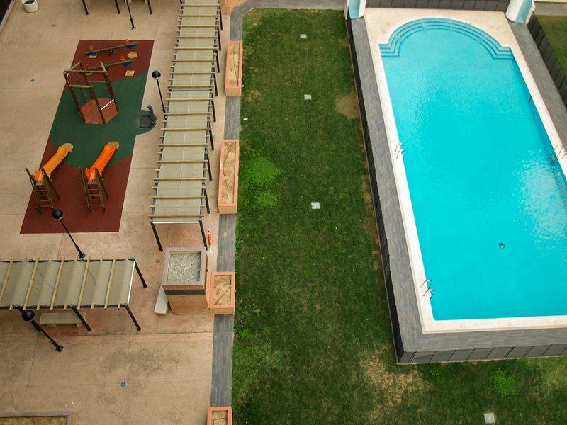 Vistas a la piscina parque infantil. Vues de la piscine et aire de jeux pour les enfants.