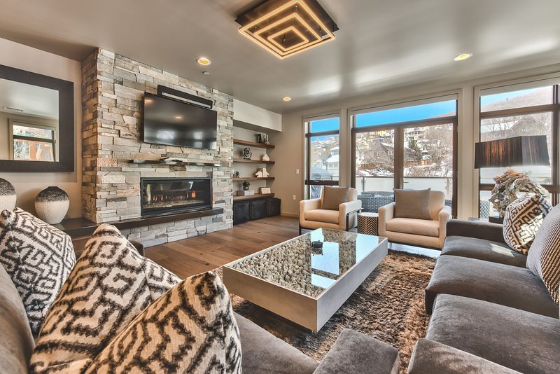 Professionally Decorated Living Room with 60' Smart TV, Sonos PlayBar, Comfortable Furnishings, Gas Fireplace, and a Private Deck Overlooking Main Street