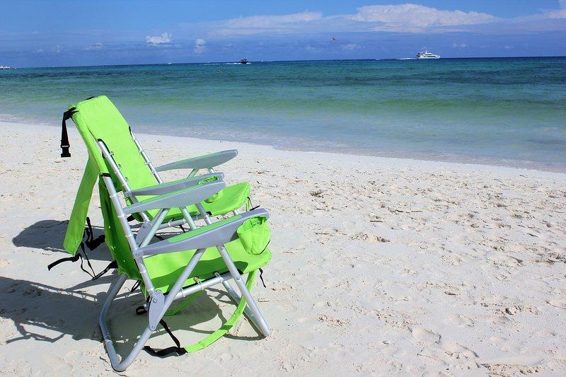 Estas sillas de playa portátiles se proporcionan para su disfrute en este local de la playa - también toallas de playa