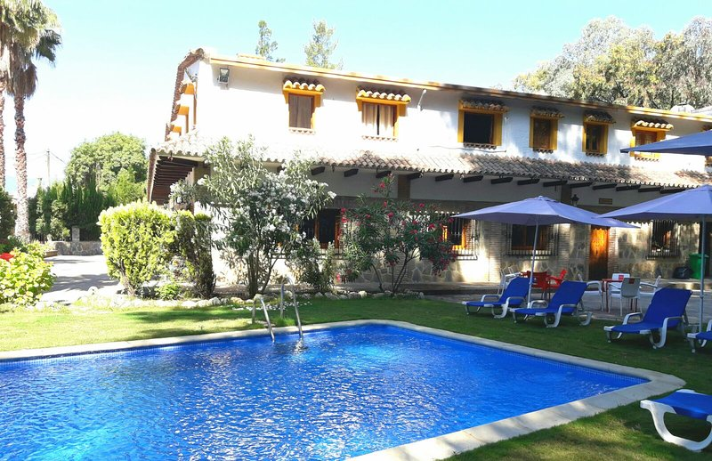 Piscina exterior con tumbonas, sombrillas y jardines.