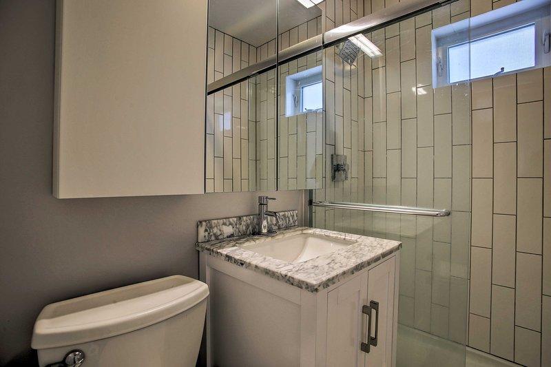 O banheiro tem uma pia de granito, vaidade único, e uma cabine de duche forrado de azulejos.