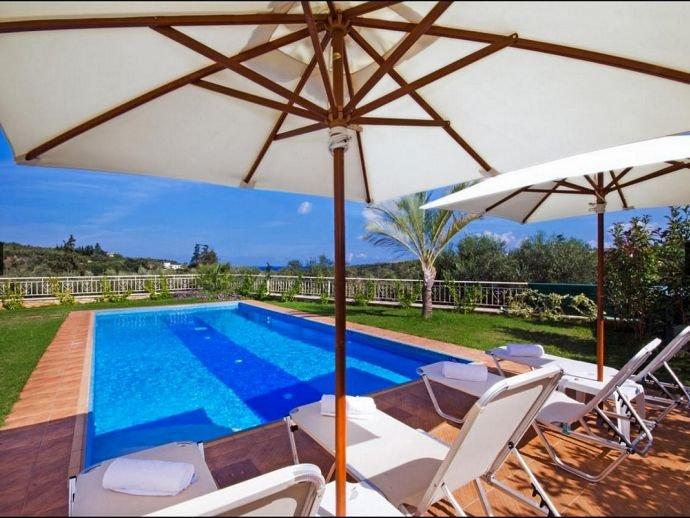Prive zwembad met ligstoelen en parasols