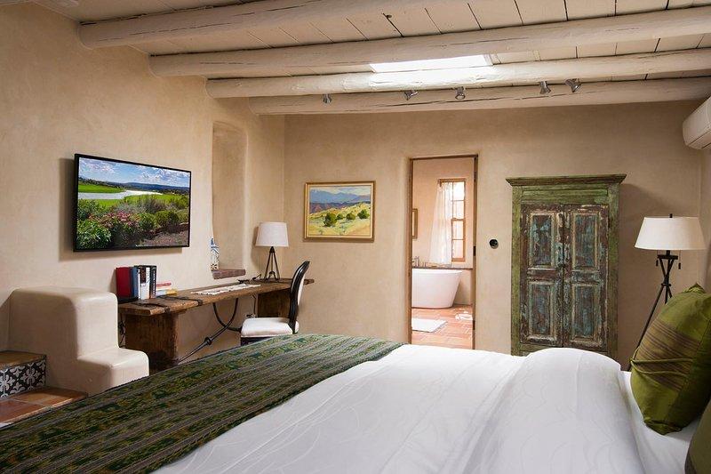 Uma das duas suites rei é generoso em tamanho, tem uma mesa de trabalho, montar grande parede TV, com a casa de banho privativa para trás.