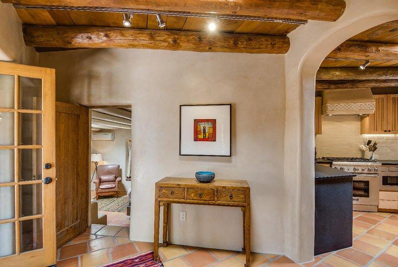 Voltar para a entrada com um quarto à esquerda, cozinha em frente e salas de estar e jantar à direita.