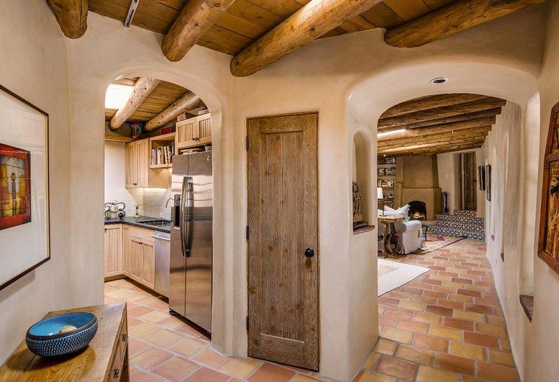 Entrar na casa para esse foyer angular com uma suite rei da esquerda, cozinha em meio e estar-jantar área à direita da.