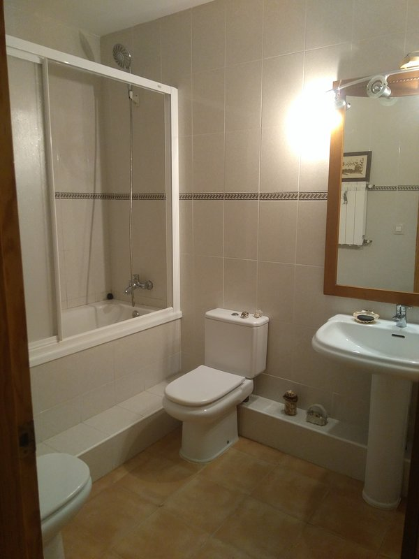 Huvudsakliga badrum med badkar och dusch