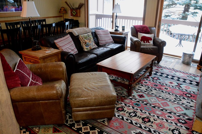 Comfortable leather chairs and couch facing fireplace