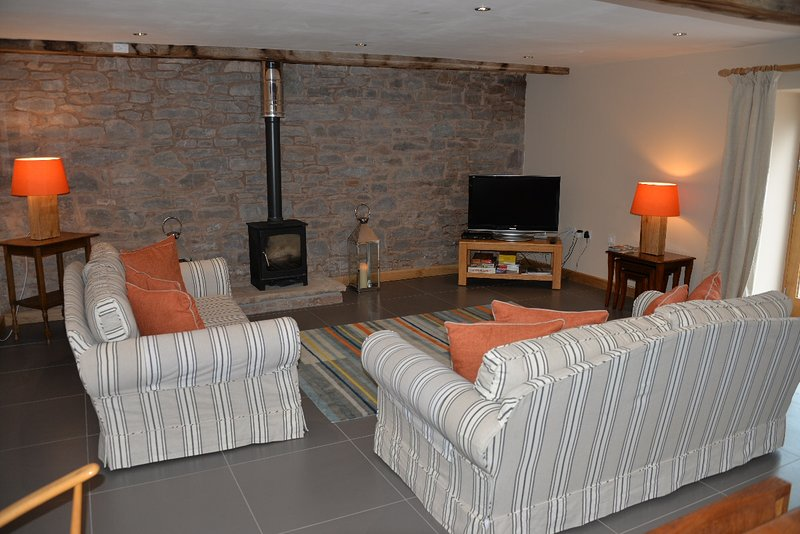 The living room has a log burner, satellite TV and an additional dining area.