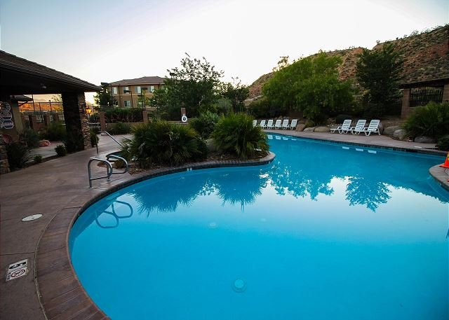 Outdoor pool and hot tub with surrounding lounge chairs