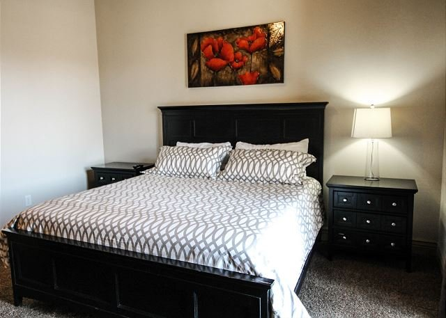 Spacious master bedroom features a king-size bed, TV, and master