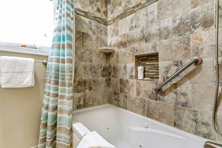 Genießen Sie ein Bad mit einem tiefen Whirlpool im Eingangsbereich, der von den Schlafzimmern 2 und 3 geteilt wird.
