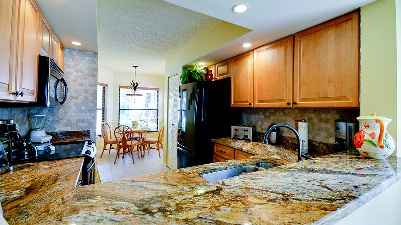 Remodeled fully-supplied kitchen with spectacular granite counters has pass through to dining area