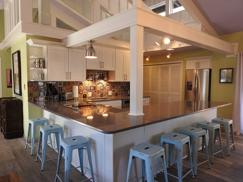 Our fully stocked gourmet kitchen offers seating for 8+ at the kitchen's quartz countertop.