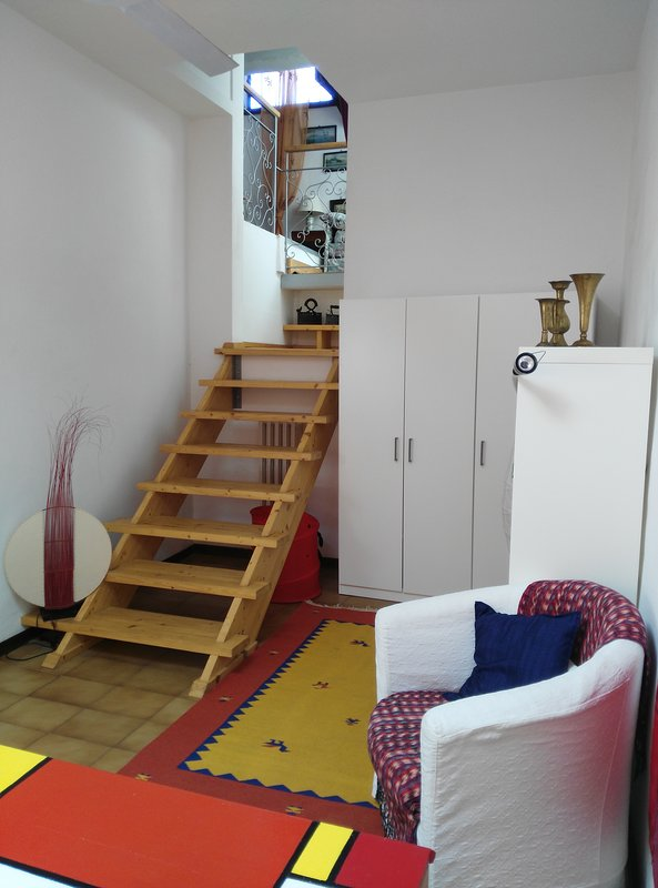 Wooden staircase connecting the bedroom to the attic lounge