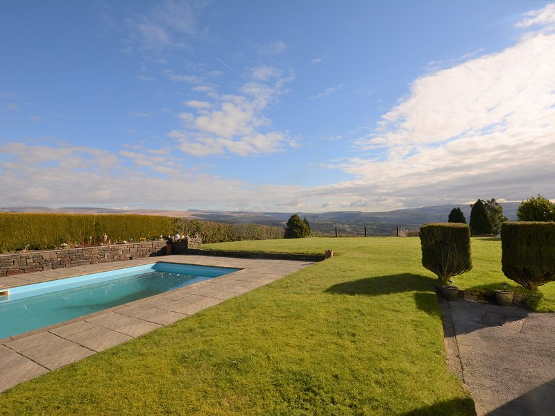 View towards the semi-detached property with large garden and swimming pool