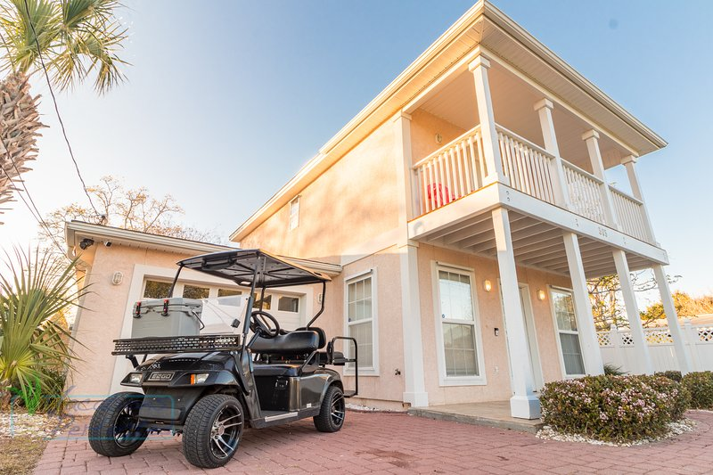 Beautiful shot of front of house and golf cart available with renting the home, extra fee for golf cart