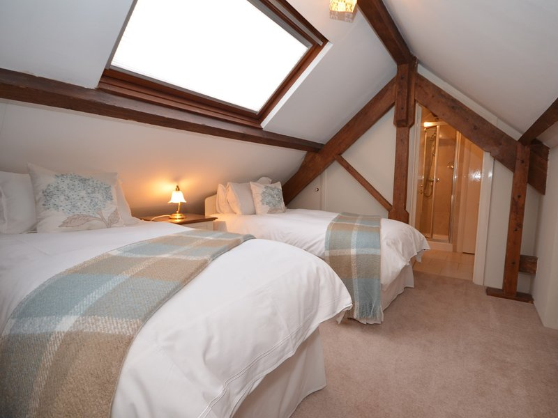 Hideaway within the eaves in the cosy twin bedroom with en-suite shower room and WC