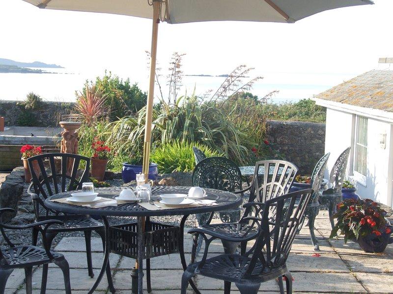 Geniet van het uitzicht op zee vanaf de gedeelde patio tuin. De ommuurde terras heeft ook zitplaatsen.