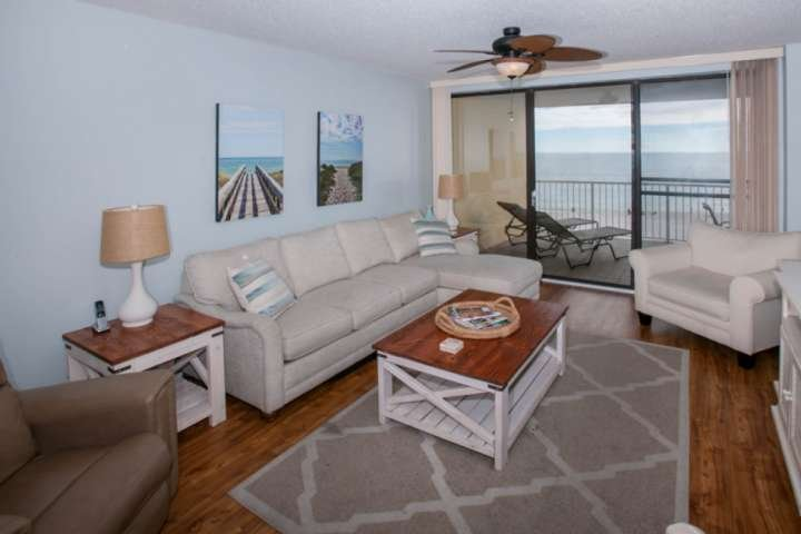 Living room with wood floors looking over Gulf front balcony