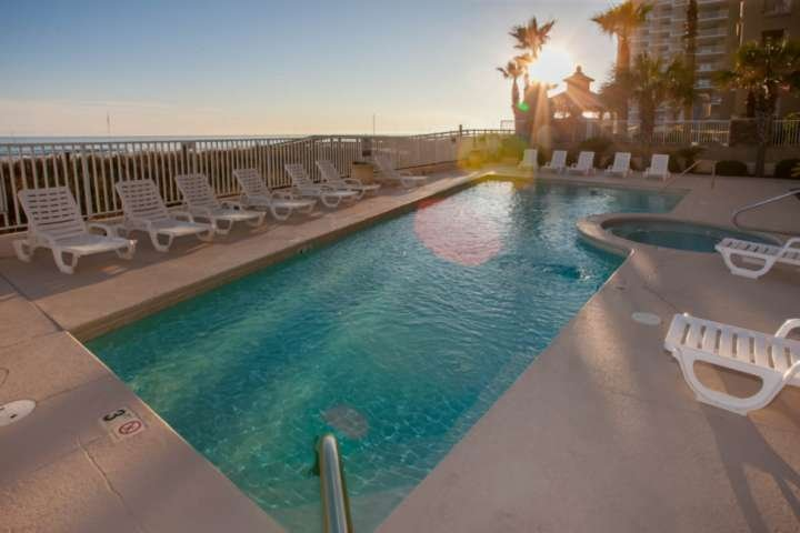 Community pool and hot tub with surrounding lounge chairs