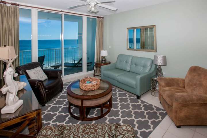 Tiled living room with sleep sofa and balcony access to Gulf front views