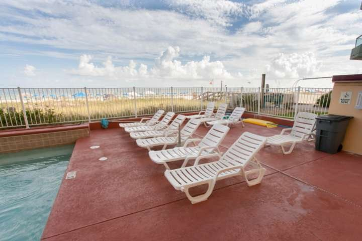 Lounge chairs at the community pool with beach and Gulf in background