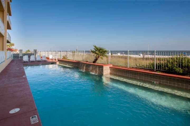 Community pool with lounge chairs overlooking the beach and the Gulf
