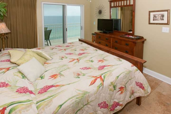 Master bedroom with flat screen TV and private patio access