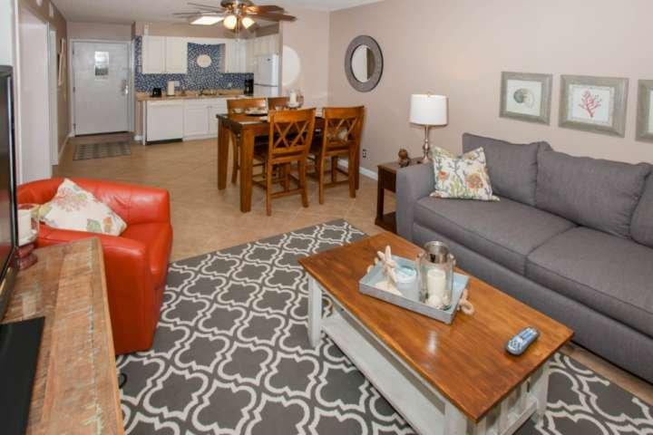 salon carrelée avec tapis, canapé 3 places, chaise, table basse, table d'extrémité, deux lampes